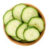 Tranches de concombre dans la cuvette en bois au-dessus du blanc Images stock