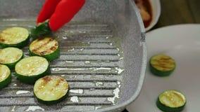 Tranches de courgette frites en beurre sur une casserole de gril banque de vidéos