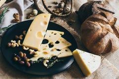Tranches de fromage parmi des écrous sur un plat élégant noir Toile à sac beige comme fond Pain rond savoureux tout près parfait images libres de droits