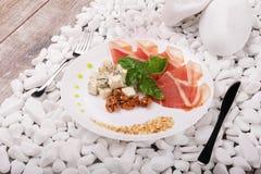 Tranches de jambon, de noix et de fromage d'un plat Un couteau et une fourchette près d'un plat sur un blanc lapide le fond dîner Photos libres de droits