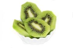 Tranches de kiwi dans une soucoupe sur un fond blanc Images stock