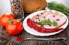 Tranches de la poitrine, du clou de girofle et du poivre noir, aneth dans le plat, tomates, ail, pain, tomates rouges, bouteille  image libre de droits