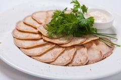 Tranches de langue de boeuf bouillie d'un plat blanc photo stock