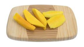 Tranches de mangue fraîche sur une planche à découper en bois photo libre de droits
