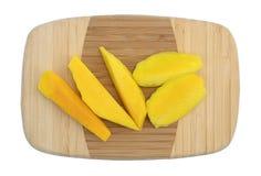 Tranches de mangue fraîche sur une planche à découper en bois photos stock