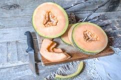 Tranches de melon mûr sur un hachoir Photo stock