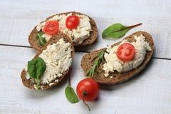 Tranches de pain avec du fromage blanc à côté des tomates Images libres de droits