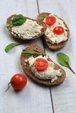 Tranches de pain avec du fromage blanc à côté des tomates Photographie stock libre de droits