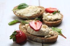 Tranches de pain avec du fromage et les fraises blancs sur le dessus Images libres de droits