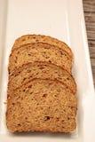 Tranches de pain de multigrain de Brown d'un plat blanc Image libre de droits