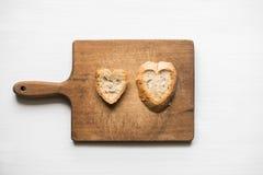 Tranches de pain en forme de coeur sur le vieux concept d'amour de planche à découper Image stock