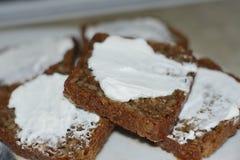 Tranches de pain enduites du fromage blanc Photos stock