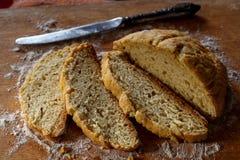 Tranches de pain et couteau sur un conseil en bois Images stock