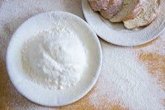 Tranches de pain et farine de blé dans un plat blanc sur la table Photographie stock