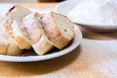 Tranches de pain et farine de blé dans un plat blanc sur la table Image libre de droits
