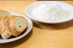 Tranches de pain et farine de blé dans un plat blanc sur la table Photos stock