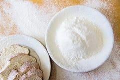Tranches de pain et farine de blé dans un plat blanc sur la table Image stock
