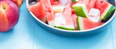 Tranches de pastèque dans un plat avec de la glace et des pêches sur un fond bleu Image stock