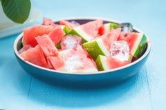 Tranches de pastèque dans un plat avec de la glace sur un fond bleu Images stock