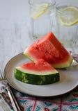 Tranches de pastèque de plat avec de l'eau l'eau glacée à l'arrière-plan Images stock