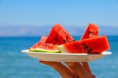 Tranches de pastèque du plat sur le fond bleu de mer Fruit frais sur la plage Style de vie sain l'été porte des fruits des vacanc photos libres de droits