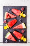 Tranches de pastèque, glace de fruit, myrtilles congelées, framboises sur le conseil noir Images stock