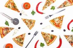 Tranches de pizza, d'ingrédients et de couverts sur un fond blanc Vue supérieure photos libres de droits