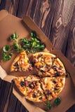 Tranches de pizza faite maison sur le carton avec le basilic sur le fond en bois Vue supérieure Plan rapproché Photo stock