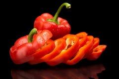 Tranches de plan rapproché de paprikas rouges sur le noir avec des gouttes de l'eau Images stock