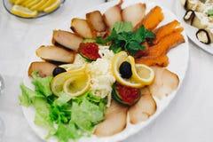 Tranches de poissons et d'olives noires d'un plat avec le citron image libre de droits