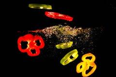 Tranches de poivre vert, rouge et jaune tombant dans l'eau image libre de droits
