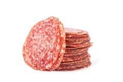 Coupe en tranches le salami d'isolement sur un blanc image libre de droits
