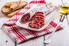 Tranches de salami d'un plat blanc Images stock