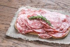 Tranches de salami sur le conseil en bois Photos libres de droits