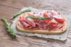 Tranches de salami sur le conseil en bois Photos stock