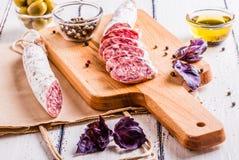 Tranches de salami sur une planche à découper Photographie stock libre de droits