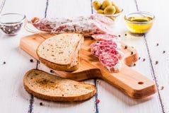 Tranches de salami sur une planche à découper Photos libres de droits