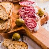 Tranches de salami sur une planche à découper Images libres de droits