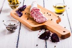 Tranches de salami sur une planche à découper Image libre de droits