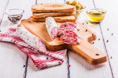 Tranches de salami sur une planche à découper Image stock