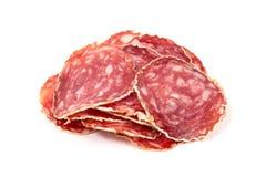 Tranches de saucisse de salami sur un fond blanc images stock