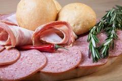 Tranches de saucisse et de lard sur une planche à découper avec des petits pains de pain, photo stock