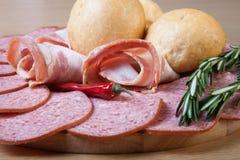 Tranches de saucisse et de lard sur une planche à découper avec des petits pains de pain, photos libres de droits