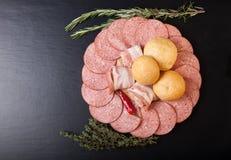 Tranches de saucisse et de lard sur une planche à découper avec des petits pains de pain, photographie stock libre de droits