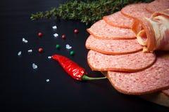 Tranches de saucisse et de lard sur une planche à découper ronde avec le rosema image stock