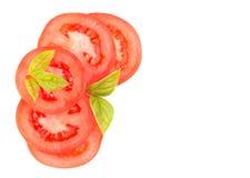 Tranches de tomate avec des feuilles de basilic, dans le coin avec l'espace de copie Images stock