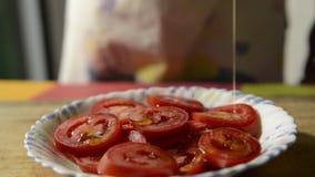 Tranches de tomate habillées avec l'huile d'olive banque de vidéos