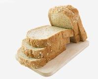 Tranches entières de pain de grain sur la planche à découper en bois Image stock