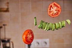 Tranches et tomate de concombre dans le vol gratuit dans la cuisine Photos libres de droits