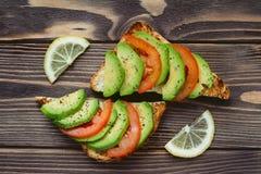 Tranches fraîches d'avocat et de tomate avec du pain sur une table Image libre de droits